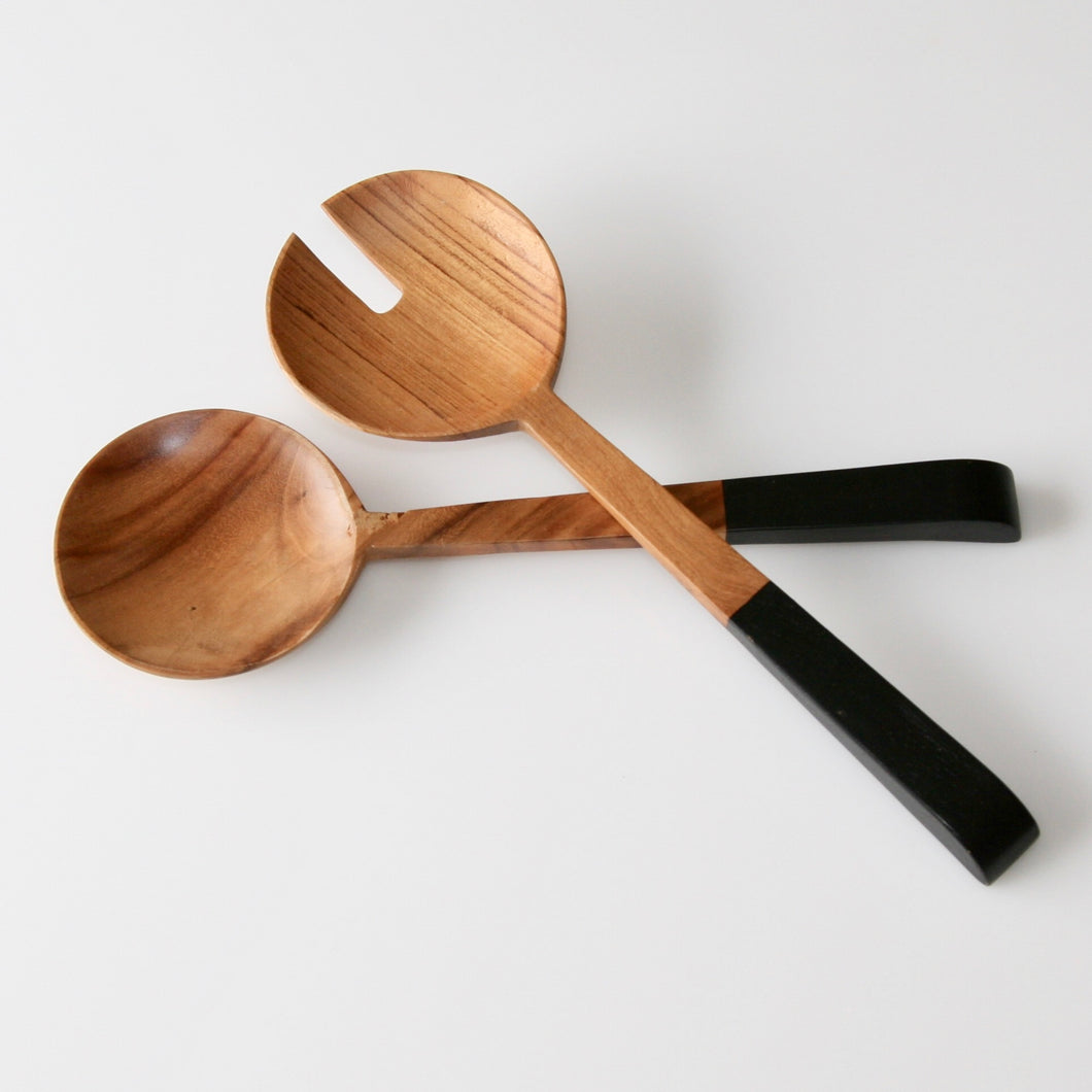 Set of two carved natural oiled teak salad servers finished with either black or grey painted handles