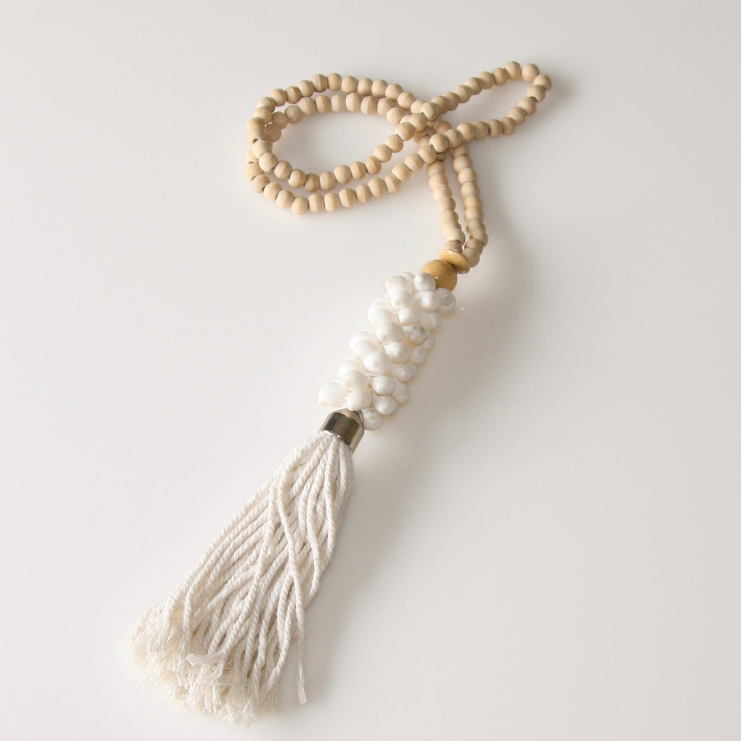 Handmade beaded shell necklace hanging featuring small white wooden beads strung with a selection of small white shells and large cotton tassel.