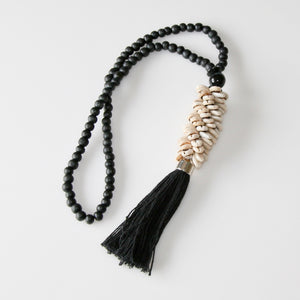 Handmade beaded shell necklace hanging featuring small black wooden beads strung with a selection of small natural shells and large black cotton tassel.