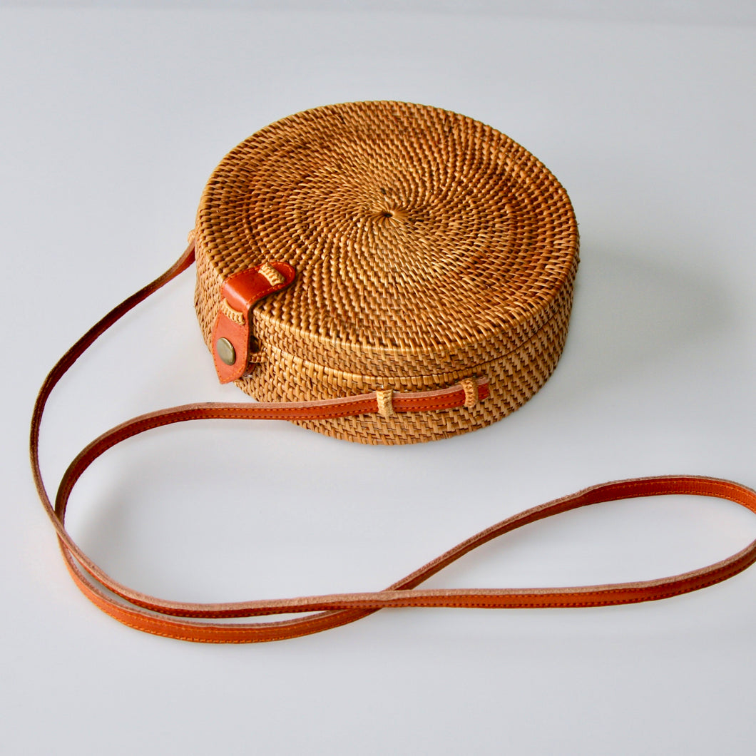 Round rattan ata crossbody handbag in natural colour with tan leather snap closure and long tan leather body strap