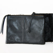 Load image into Gallery viewer, Black rectangular clutch with cowhide leather on one side and suede on the reverse finished with leather pull on zipper closure