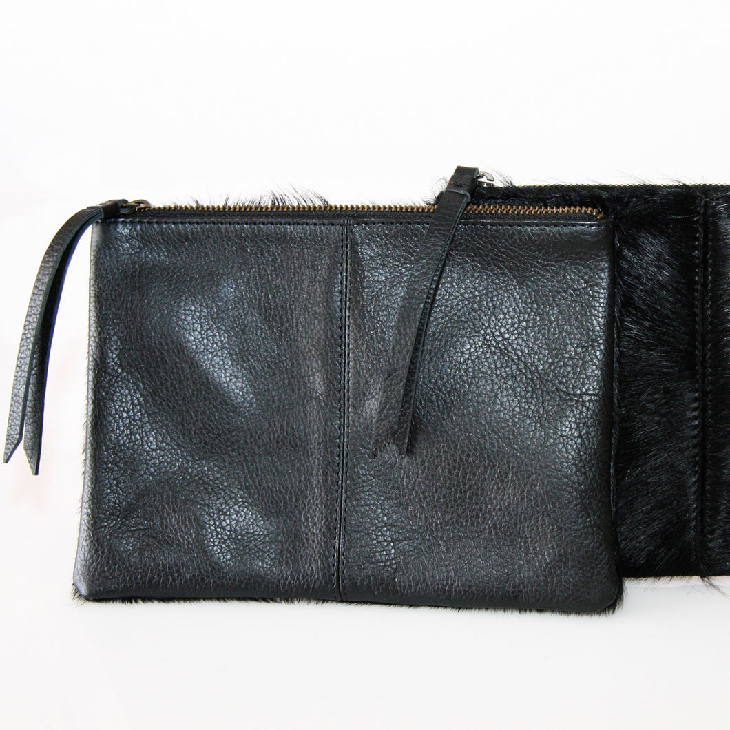 Black rectangular clutch with cowhide leather on one side and suede on the reverse finished with leather pull on zipper closure