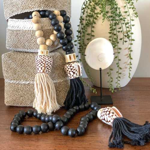 Beaded cowrie shell tasselled necklace hangings perfect for adding a luxe tribal coastal look to your decor. Handmade using wooden beads strung with a unique tiger cowrie shell and large cotton tassel.