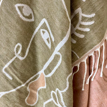 Load image into Gallery viewer, Olive and blush pink coloured throw featuring an abstract femme faces design. Super soft and super stylish, it features a fringed edge on opposite ends.