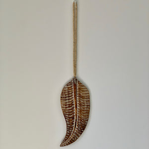 Large wooden hand carved leaf decoration hanging on a beaded garland.
