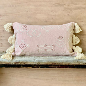 Oblong blush pink boho coastal cushion with white and dusty rose coloured embroidered stitching and finished with four white soft tassels on the two shorter edges.