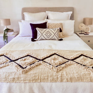 Bold and unique boho coastal custom handmade diamond tufted bed runner made from thick natural cotton and featuring a black diamond pattern across the length of the runner amidst a thick tufted pattern.