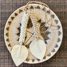 Load image into Gallery viewer, Handmade long tassels made from twine strung with a selection of small white or natural shells and a cotton macrame tassel shaped into a flat leaf. Long tassels are styled on a woven rattan tribal plate.