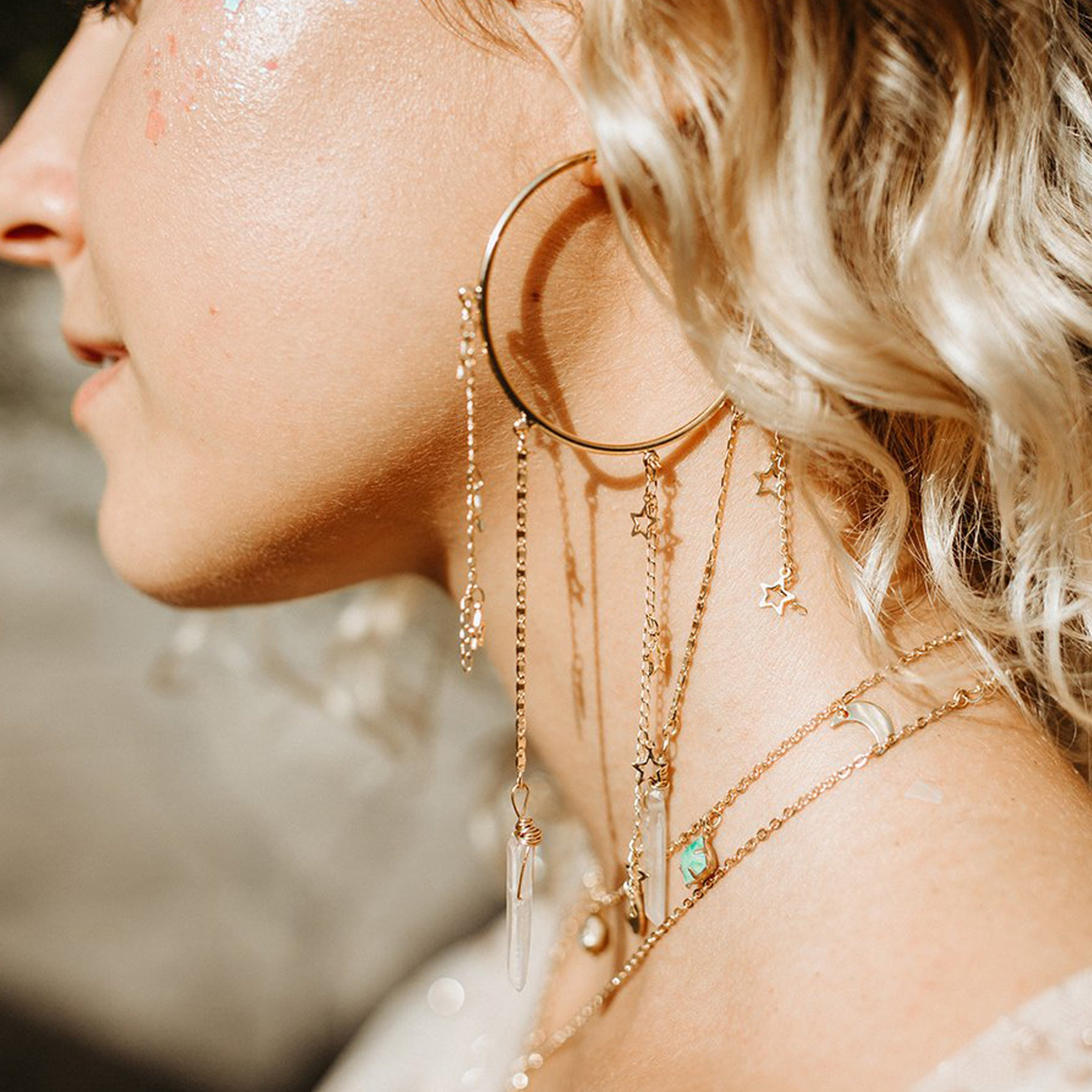beautiful model wearing baddest bish ever fine jewelry dreamy dream catcher clear quartz crystal 16 karat gold earrings in dreamy dreams catcher collection