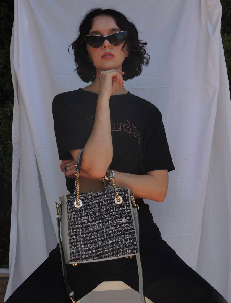 black outfit and vegan leather and tweed handbag