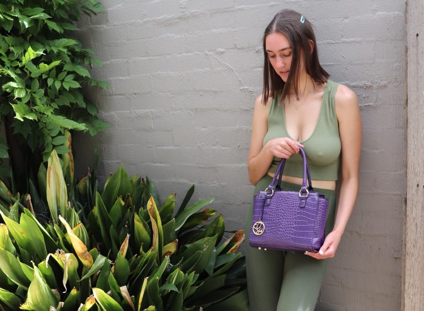 sage green co-ord outfit styled with a purple vegan handbag