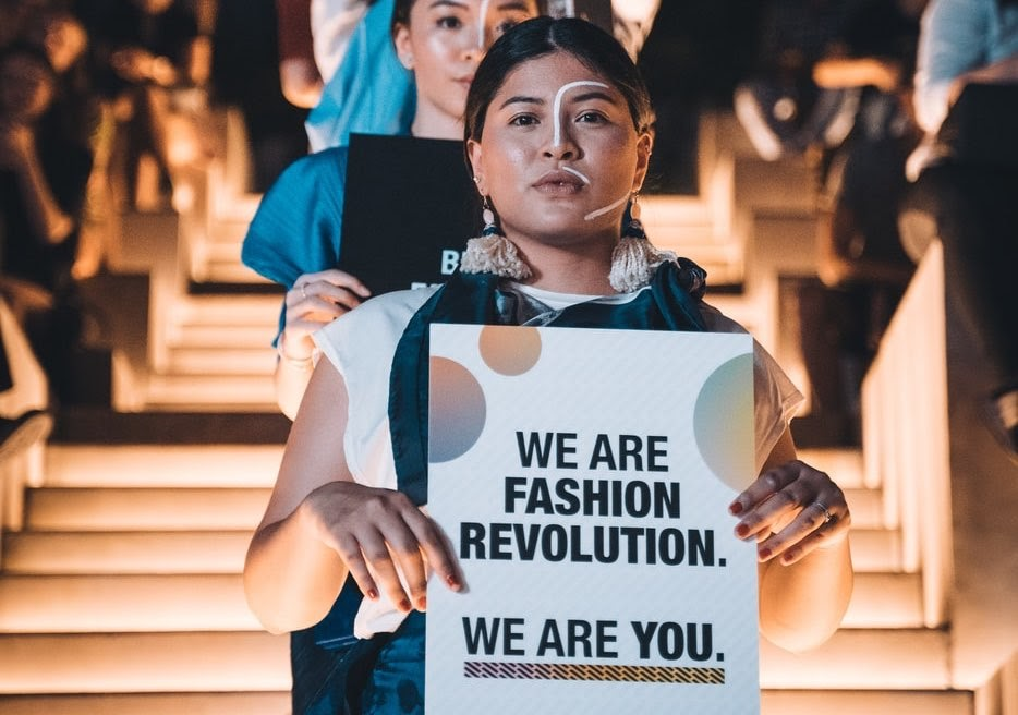 model activists on runway holding fashion revolution signs