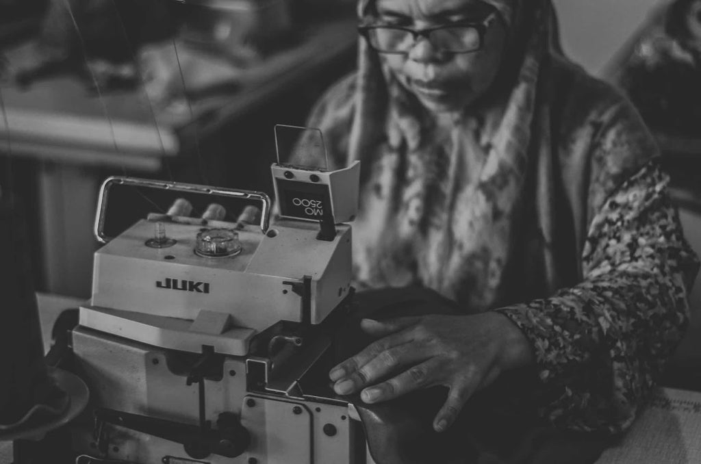 garment worker sewing black and white photo