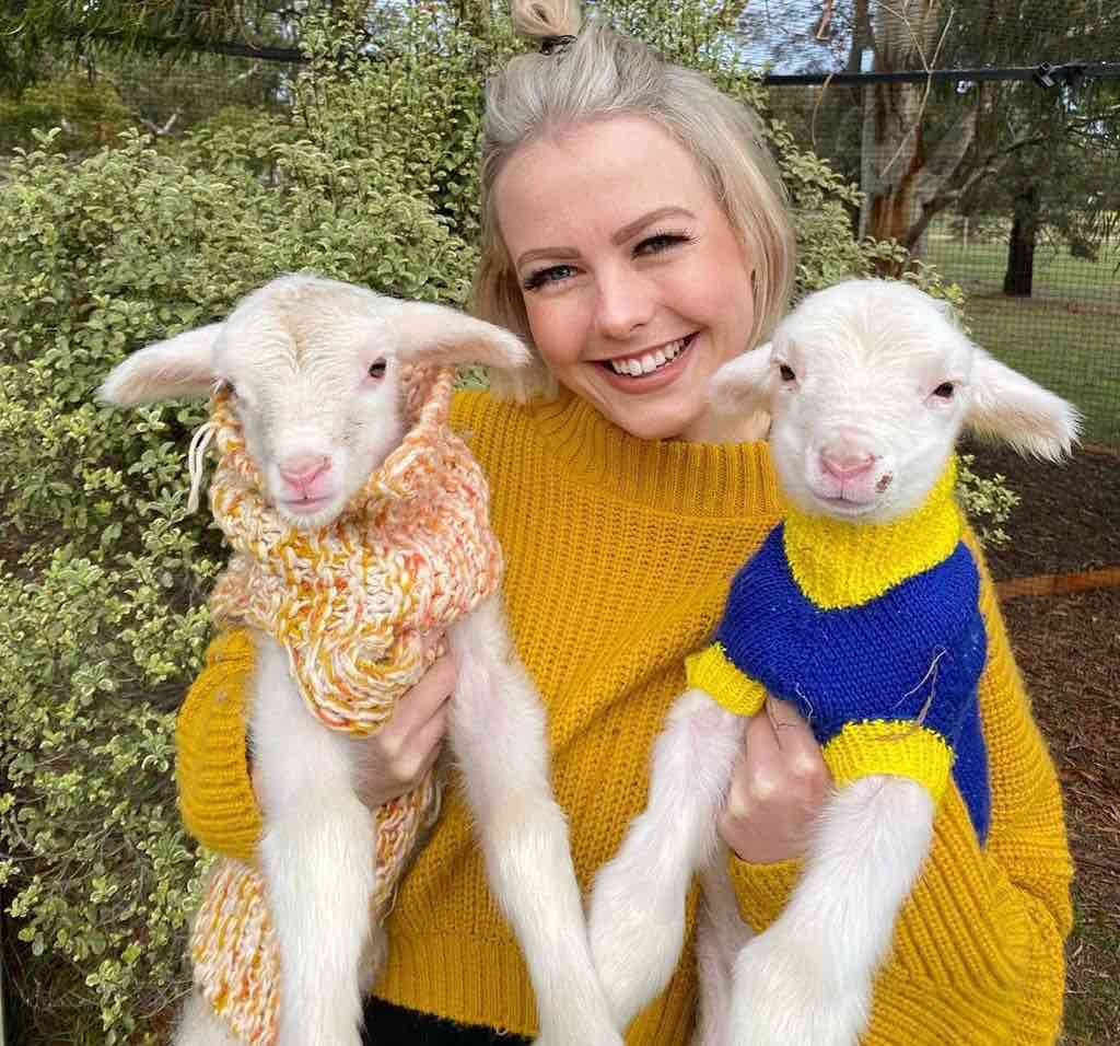 georgie purcell and newborn lambs in jumpers