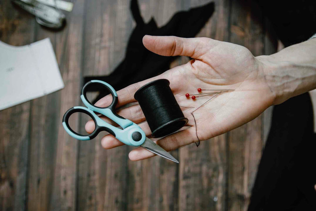 hand holding scissors and twine to mend clothes with