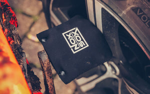 Nox Sox covered pedal resting against a car wheel