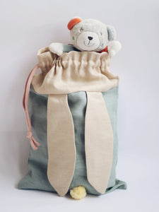 bunny bag in sage green linen with bunny ears and fluffy tail. Great to use as slippers bag, toys bag or diaper container.