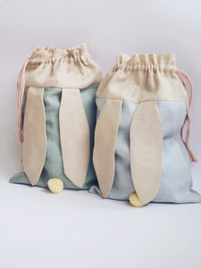 bunny bags in sage green and baby blue linen with bunny ears and fluffy tail. Great to use as slippers bag, toys bag or diaper container.