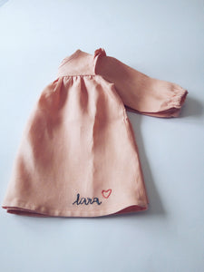 Korana linen long sleeves dress in peachy pink with customized hand embroidered name by Zekko Kids Clothes. Ruffles details on shoulders. Wooden buttons.