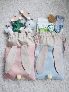 bunny bag in peachy pink and baby blue linen with bunny ears and fluffy tail. Great to use as slippers bag, toys bag or diaper container.