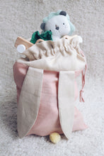 Load image into Gallery viewer, bunny bag in peachy pink linen with bunny ears and fluffy tail. Great to use as slippers bag, toys bag or diaper container.