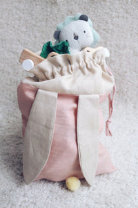 bunny bag in peachy pink linen with bunny ears and fluffy tail. Great to use as slippers bag, toys bag or diaper container.