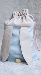 bunny bag in baby blue linen with bunny ears and fluffy tail. Great to use as slippers bag, toys bag or diaper container.