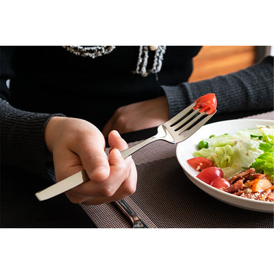 Hand holding titanium fork with cherry tomato.
