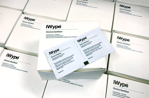 close-up of iWype 70% isopropyl alcohol wipe in packaging atop multiple boxes
