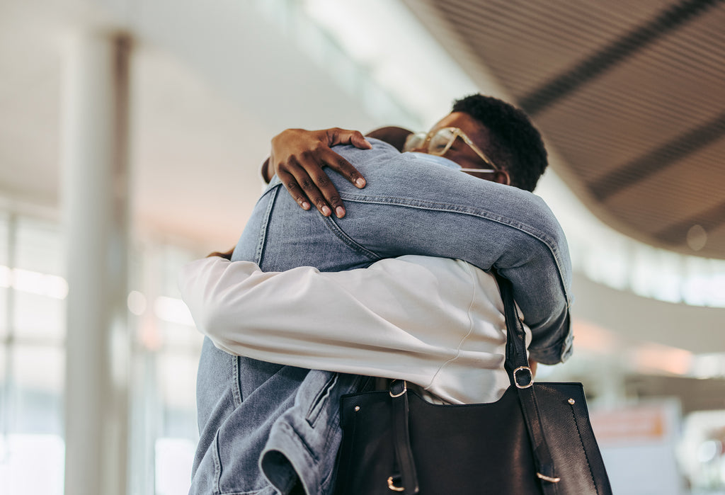 Stock photo of a couple meeting at airport arrival gate