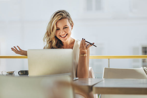 Businesswoman looking at laptop and smiling at cafe