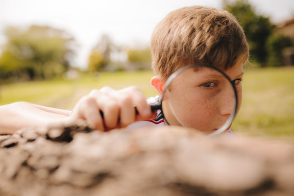 Boy exploring with magnifying glass