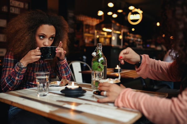 Young woman drinking coffee at cafe