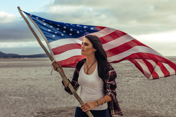 Woman holding a USA flag on the beach