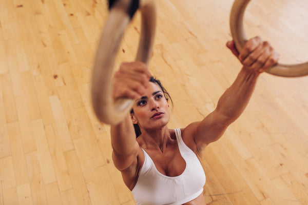Determined young woman at gym using gymnastic rings