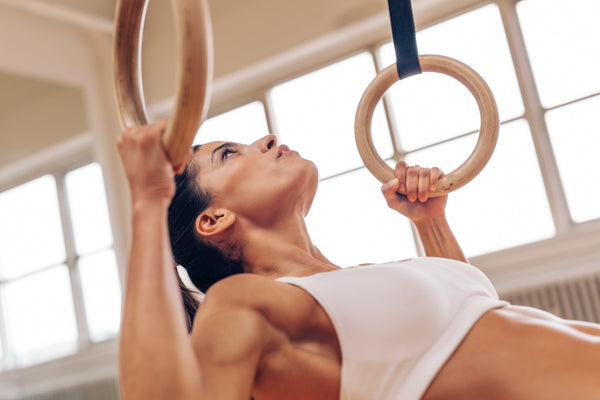 Strong woman doing pull-ups with gymnastic rings