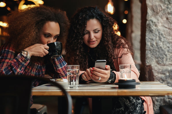 Young friends sitting in a cafe looking at a smartphone