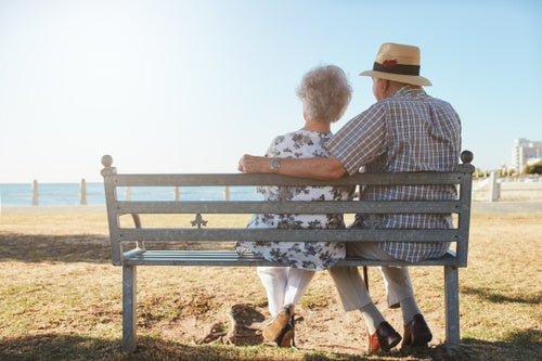 Elderly couple relaxing on a bench looking out to sea