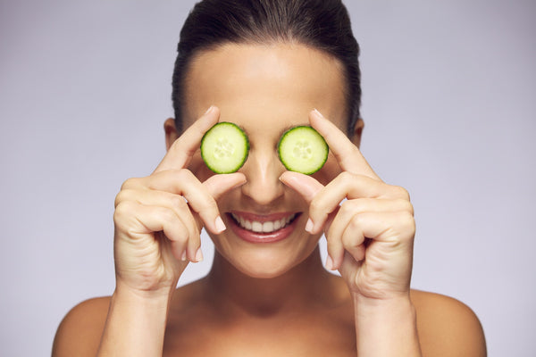 Woman holding slices of cucumber over eyes