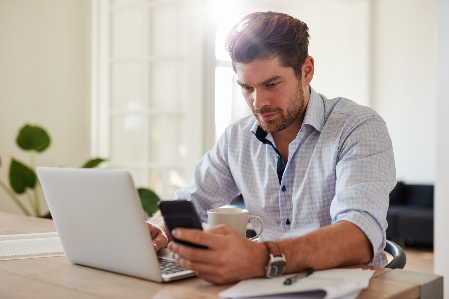 Young man working with laptop and mobile phone at his home office ...