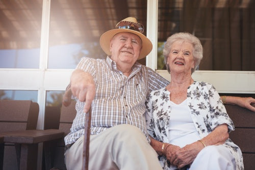 Loving retired couple relaxing on a bench outside their house