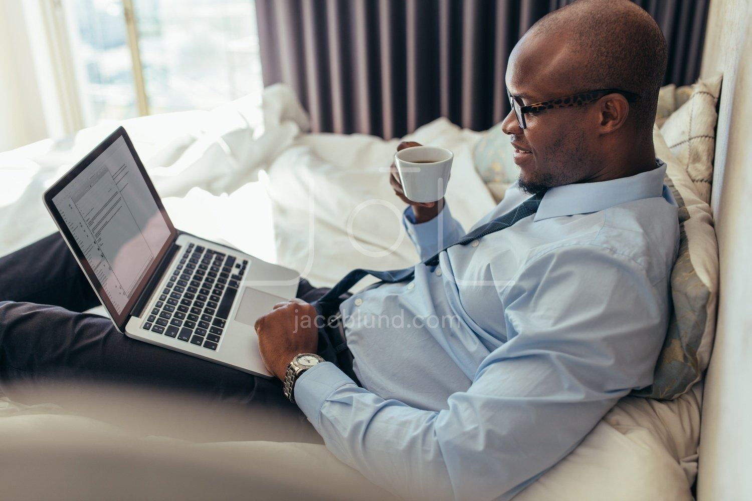 Businessman working on laptop computer lying on bed – Jacob Lund ...