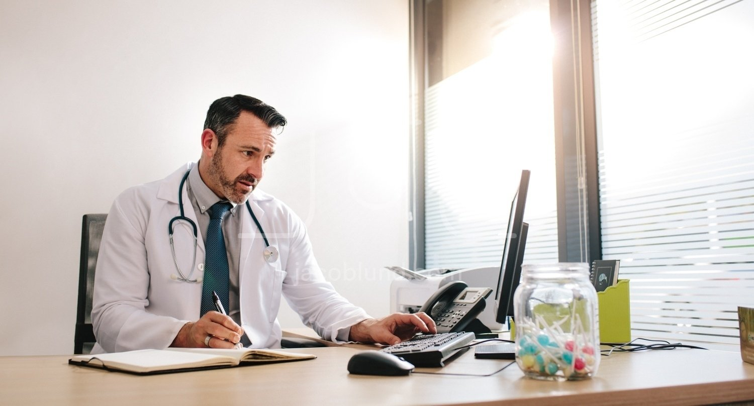 Doctor working at his clinic desk Jacob Lund Photography Store- premium stock photo