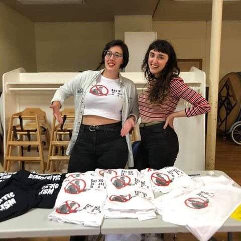 Two grown women selling joke shirts at a poorly attended flea market organized by one of them.