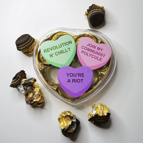 "Half empty clear plastic heart-shaped box of chocolates on white background with wrappers and half-eaten chocolates strewn about and three candy heart stickers with ""revolution n chill"", ""join my communist polycule"", and ""you're a riot"" on top of the box."