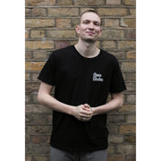 Front of man wearing black short sleeve organic cotton t-shirt with white Goose Studios logo on left chest