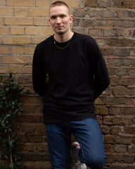 Man standing wearing black organic cotton long sleeve t-shirt with blue jeans.
