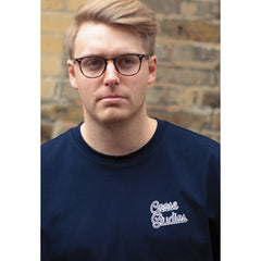 Close up of a man wearing navy blue organic cotton long sleeve t-shirt with white printed logo