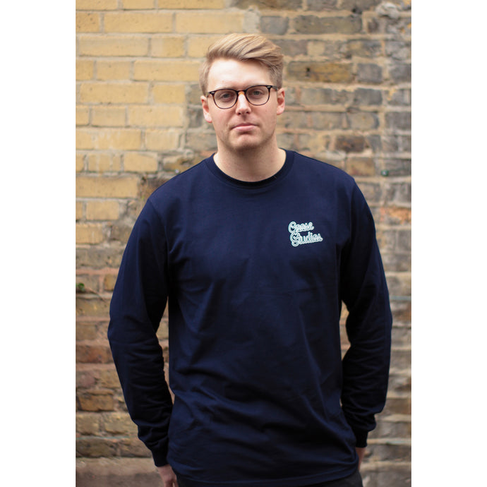 Man with glasses wearing relaxed fit navy blue organic cotton long sleeve t-shirt with white printed logo
