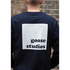Back of man wearing navy blue organic cotton long sleeve t-shirt with large white square Goose Studios logo